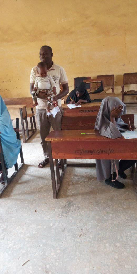 See Photos Of Nigerian Teacher Babysitting Student's Baby As She Writes JSS3 BECE Exam, Conquest Online Magazine